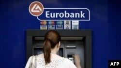 Žena podže novac sa bankomata u Atini