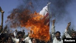 Afghan villagers burn a U.S. flag during a protest against NATO raids.