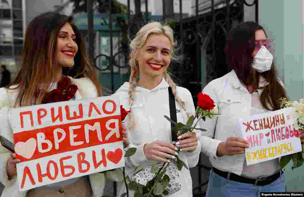 "Women attend a rally in in Moscow on August 15 to show solidarity with Belarusian protesters. The sign on the left reads: ""The time for love has come."" The sign on the right says: ""Women are peace and love. Long live Belarus."""