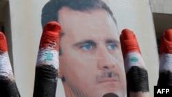 Siriýanyň prezidenti Başar al-Assadyň tarapdarlary Damaskdaky ýöriş mahalynda V-nyşanyny görkezýärler, 29-njy mart.