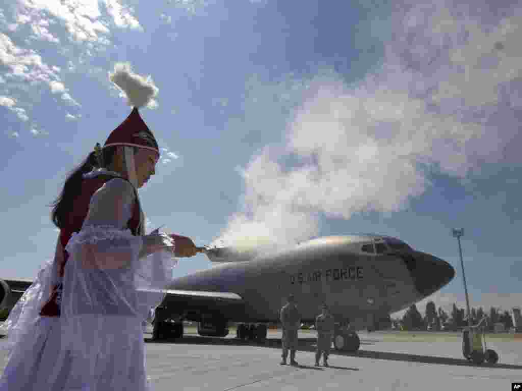 A Kyrgyz woman at Manas International Airport performs a traditional ritual during a ceremony to mark the opening of a new U.S. Army aircraft ramp on June 23. Photo by for Vladimir Voronin for AP