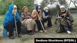 Участницы голодовки против сноса сидят во дворе в ожидании выселения и сноса. Астана, 15 августа 2014 года.