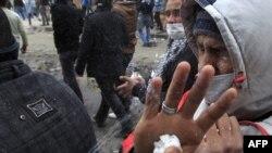Наразылық акциясындағылардың бірі көзден жас ағызатын газдан қорғанып бетіне сүт шашып жатыр. Каир, 3 ақпан, 2012 жыл.