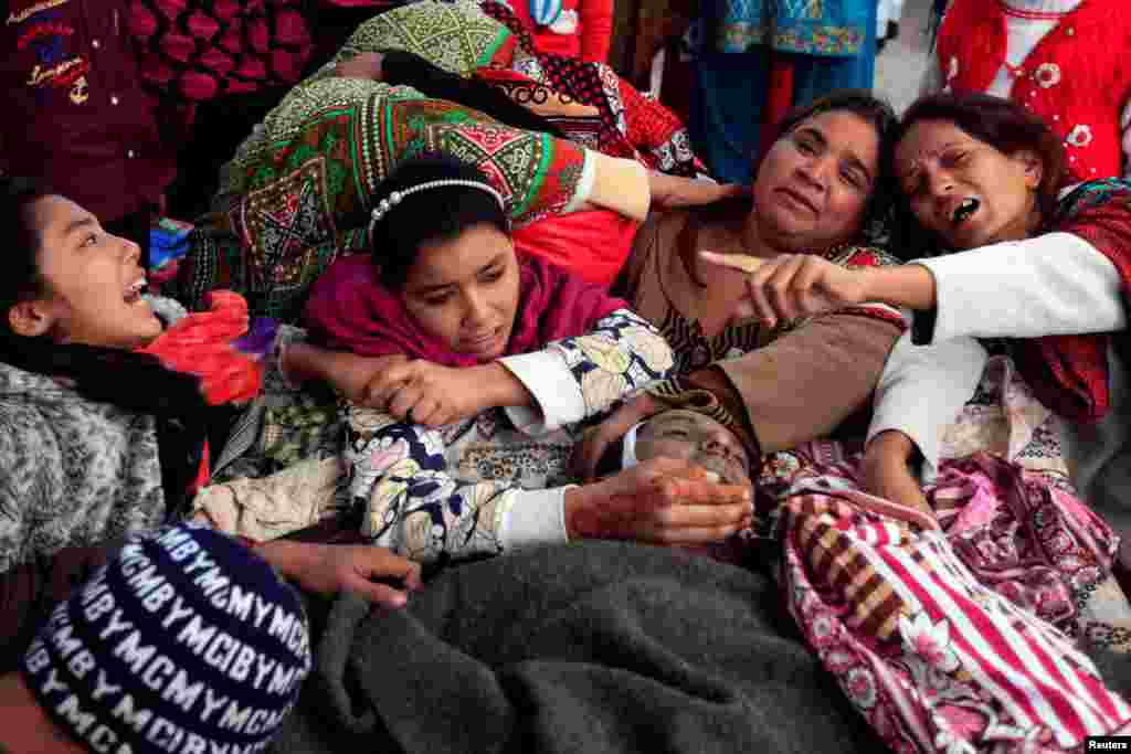 Family members mourn over the body of a relative who died after consuming locally made toxic liquor in Toba Tek Singh, Pakistan. (Reuters/Fayyaz Hussain)