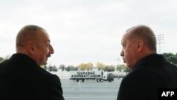 A picture taken last month shows Turkish President Recep Tayyip Erdogan (right) and Azerbaijani President Ilham Aliyev attending a military parade in Baku marking Azerbaijan's declared victory against Armenia over the breakaway Nagorno-Karabakh region.