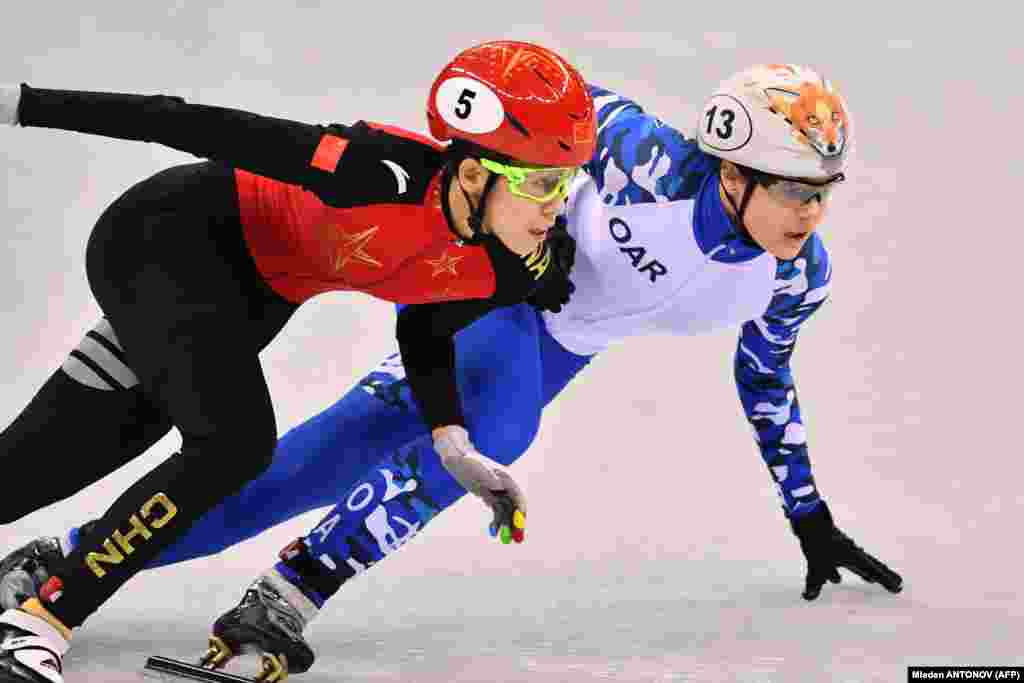Скоростное катание на коньках: китайка Фан Кексин (слева) и россиянка София Просвирнова соревнуются в женских гонках на дистанции 500 метров в четвертьфинале. Золото получила итальянка Арианна Фонтана