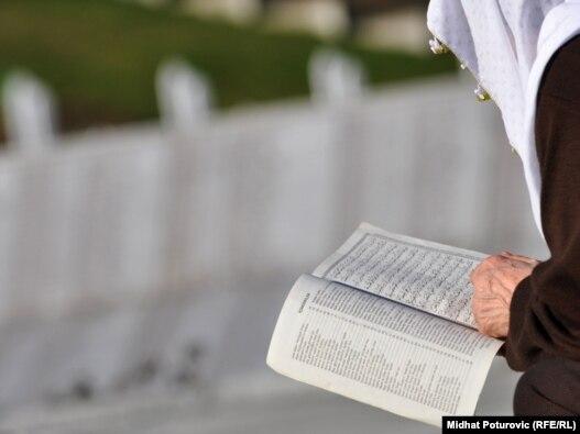 Starija žena čita molitvu u Memorijalnom centru Potočari