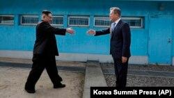 Lideri verikorean, Kim Jong Un (majtas) dhe presidenti jugkorean Moon Jae-in në zonën kufitare mes dy Koreve.