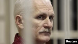 Human rights activist Ales Byalyatski sits in a guarded cage in a courtroom in Minsk during his trial in November 2011.