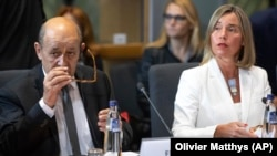 BELGIUM -- European Union foreign policy chief Federica Mogherini, right, sits next to France's Foreign Minister Jean-Yves Le Drian, during a meeting of the foreign ministers from Britain, France and Germany with the Iran Foreign Minister, at the Europa