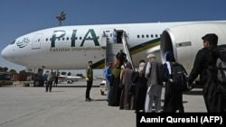 Passengers board a Pakistan International Airlines (PIA) flight, the first commercial international flight since the Taliban retook power last month, at the airport in Kabul on September 13.