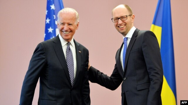 Ukrainian acting Prime Minister Arseniy Yatsenyuk (right) welcomes U.S. Vice President Joe Biden before their meeting in Kyiv today.