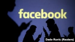 Silhouettes of mobile users are seen next to a screen projection of Facebook logo - generic