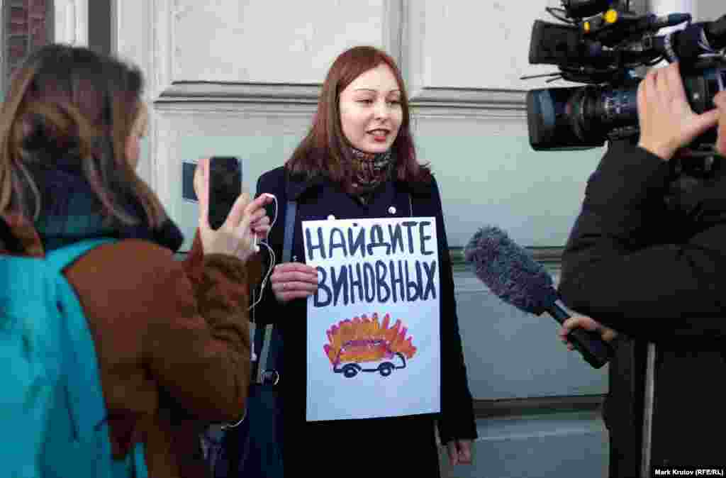 Нападники спалили мікроавтобус, на якому журналісти і правозахисники їхали з аеропорту «Беслан» в Грозний (з плакатом стоїть журналіст Анастасія Зотова)