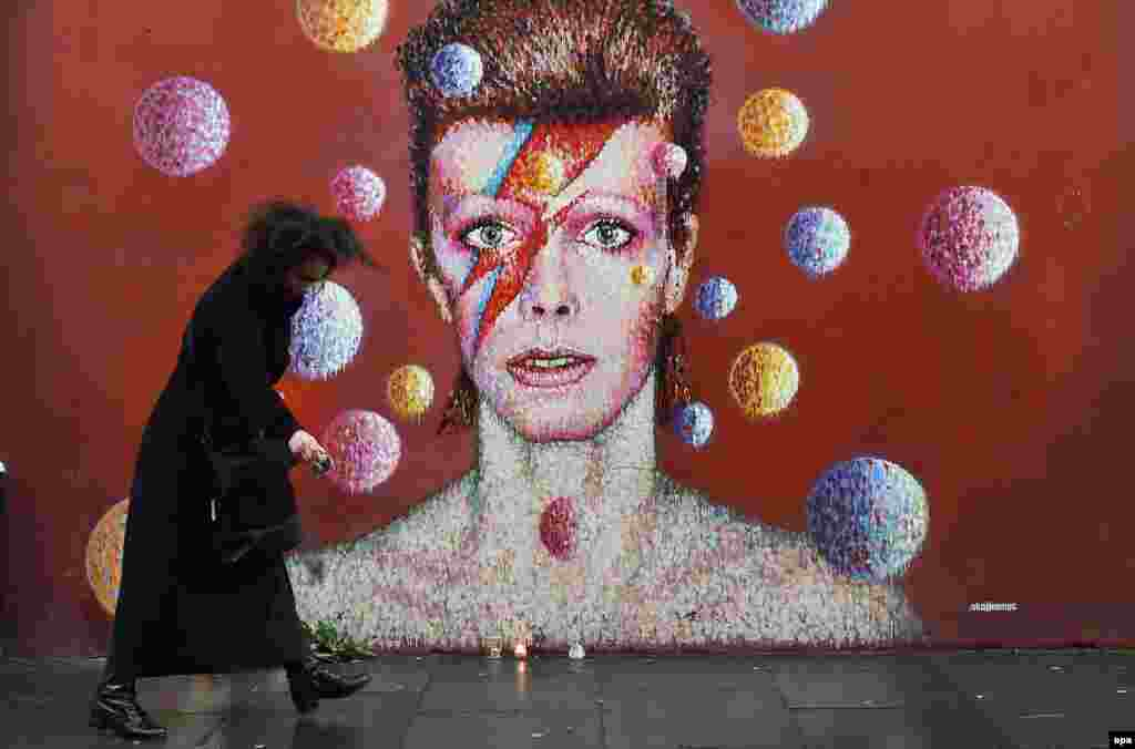 A fan sprinkles black pepper at a mural of British singer David Bowie in his hometown of Brixton, London, on January 11, after the announcement of the singer's death from cancer at the age of 69. (epa/Andy Rain)