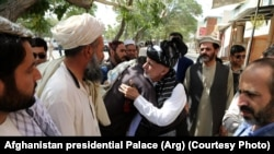 President Ashraf Ghani (center) is greeted during his trip to Ghazni Province on August 17.