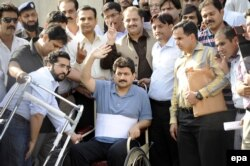 Mir, in a wheelchair, leaves after appearing before a judicial commission that is investigating an attack against him in 2014.