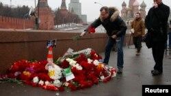 Люди приносят цветы к месту убийства оппозиционного политика Бориса Немцова в Москве.
