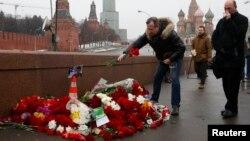 Борис Немцов қаза тапқан жерге гүл қойып жатқан ер адам. Мәскеу, 28 ақпан 2015 жыл.