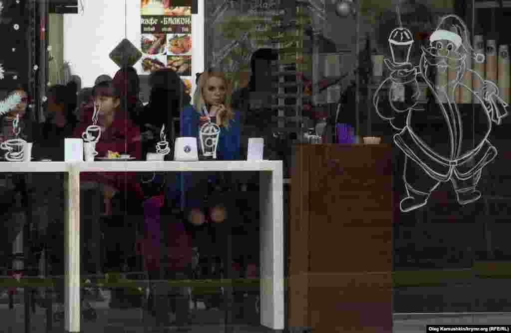 Несколько кафе продолжили работу, но посетители сидят без освещения и в тишине.
