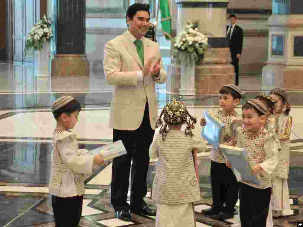 Keeping it clean: Berdymukhammedov gives presents to children during the opening ceremony of a new presidential palace in Ashgabat last year.