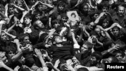FILE PHOTO: A man is carried at the site in Masala square where the body to Ayatollah Khomeini lies in state, in Tehran, Iran, June 5, 1989. REUTERS/Yannis Behrakis