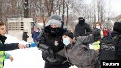 Čovek s medijskom identifikacijom drži mikrofon dok policija privodi demonstranta na skupu podrške ruskom opozicionom lideru Alekseju Navaljnom, Sankt Peterburg 31. januara.