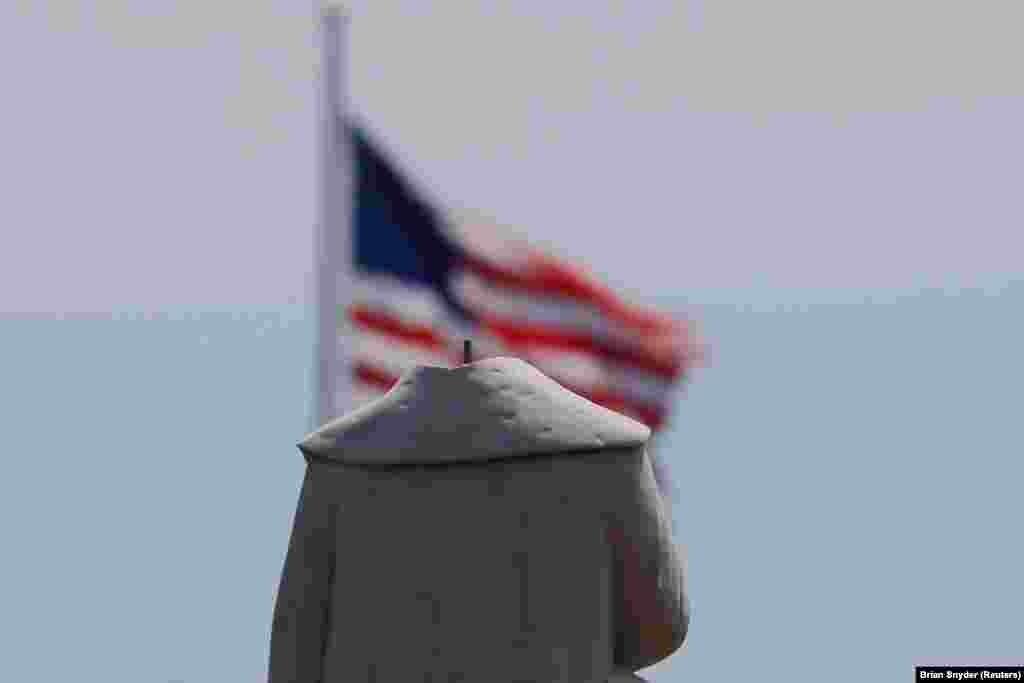 Рештки пам'ятника Христофорові Колумбу в Бостоні, штат Массачусетс, фото 10 червня 2020 року. Голову йому збили демонстранти попереднього вечора. Наступного дня місто зняло рештки пам'ятника на зберігання, поки не буде вирішено, що з ним робити далі і як «оцінити історичне значення» пам'ятника. Це був уже не перший вандальський акт щодо цього пам'ятника: його не раз обливали червоною фарбою чи обписували словами «вбивця», а одного разу вже відбивали йому голову.