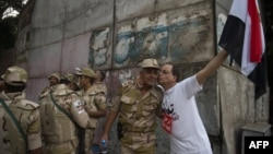 An Egyptian man welcomes an army soldier upon his deployment on a street leading to Cairo University on July 3.