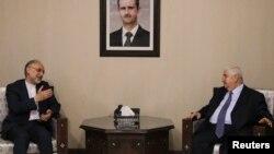 Валід аль-Муаллем (п) і Алі Акбар Салегі (л) на зустрічі в Дамаску 19 вересня 2012 року; Башар аль-Асад дивиться з портрета