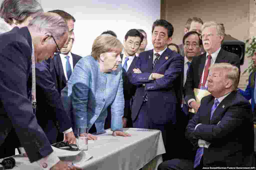 In this photo made available by the German Federal Government, German Chancellor Angela Merkel (center) speaks with U.S. President Donald Trump (seated) during the G7 summit in Quebec, Canada, on June 9. Trump angered allies by leaving the summit early and refusing to endorse a final communique that he had originally agreed to be a part of. (Jesco Denzel/German Federal Government via AP)