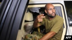 Libya -- Saif al-Islam Qaddafi appears in front of supporters and journalists at his father's residential complex in Tripoli, 23Feb2011