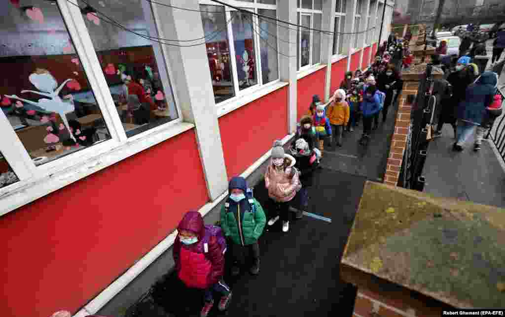 Romanian children line up outside school while waiting to disinfect their hands and enter the building during the first day of school at Cezar Bolliac Secondary School in Bucharest on February 8. (epa-EFE/Robert Ghement)
