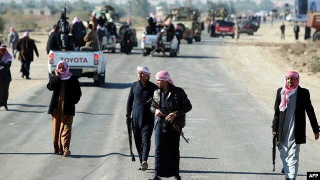Armed relatives and tribe members protect the road during a funeral procession for deputy Ayfan Saadun al-Essawi of the Al-Iraqiyah bloc in the western town of Fallujah on January 16. Essawi was killed by a suicide bomber.