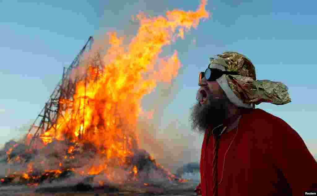 Эксцентричный российских художник Герман Виноградов сжигает масленичную пирамиду. Калужская область, Россия