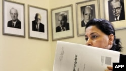 Иммигрантка из Ирана изучает опросник страноведческого теста под строгими взглядами с фотографий немецких лидеров. 310 каверзных вопросов о Германии могут поставить в затруднительное положение даже коренного немца-интеллектуала