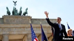 U.S. President Barack Obama waves as he arrives with German Chancellor Angela Merkel to give his speech in front of the Brandenburg Gate on Pariser Platz in Berlin on June 19.