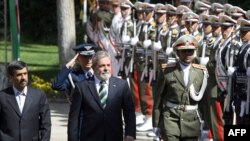 President Mahmud Ahmadinejad and his Brazilian counterpart Luiz Inacio Lula da Silva review an honour guard in Tehran