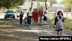 Школьники и их родители идут на линейку в День знаний.