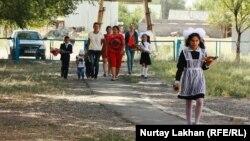 Дети идут в школу вместе с родителями. Алматинская область, 1 сентября 2014 года. Иллюстративное фото.