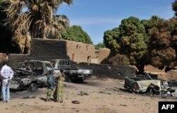 Мали тұрғындары әуеден атылған террористердің көліктеріне қарап тұр. 21 қаңтар 2013 жыл.