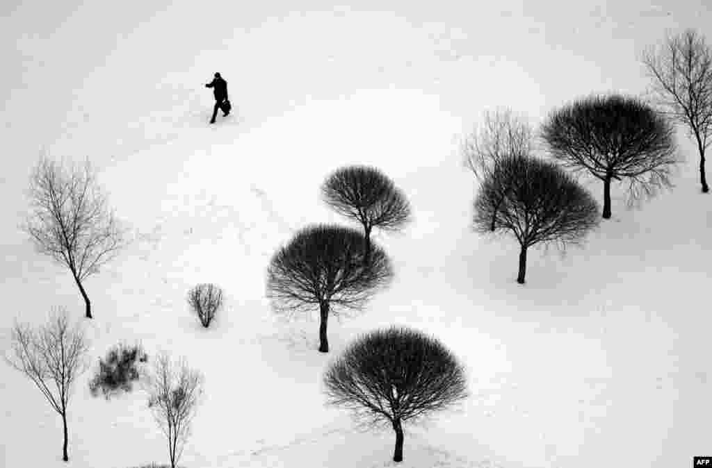 A man crosses a snow-covered park in Minsk. (AFP/Sergei Gapon)