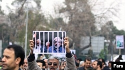A government supporter holds a poster with a picture of opposition leaders Mehdi Karrubi (left) and Mir Hossein Musavi during a demonstration in Tehran on December 30.
