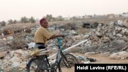 Бен Гардане базары маңындағы қоқыс жанында велосипедпен кетіп бара жатқан ер адам. 27 мамыр 2016 жыл.