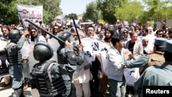 Afghan police clash with demonstrators during a protest in Kabul on June 2.