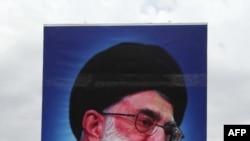 Иран ислам республикасынын түптөөчүсү, аятолла Хомейнинин портрети өкмөтчүл демонстранттын колунда. 19-июнь. Тегеран.