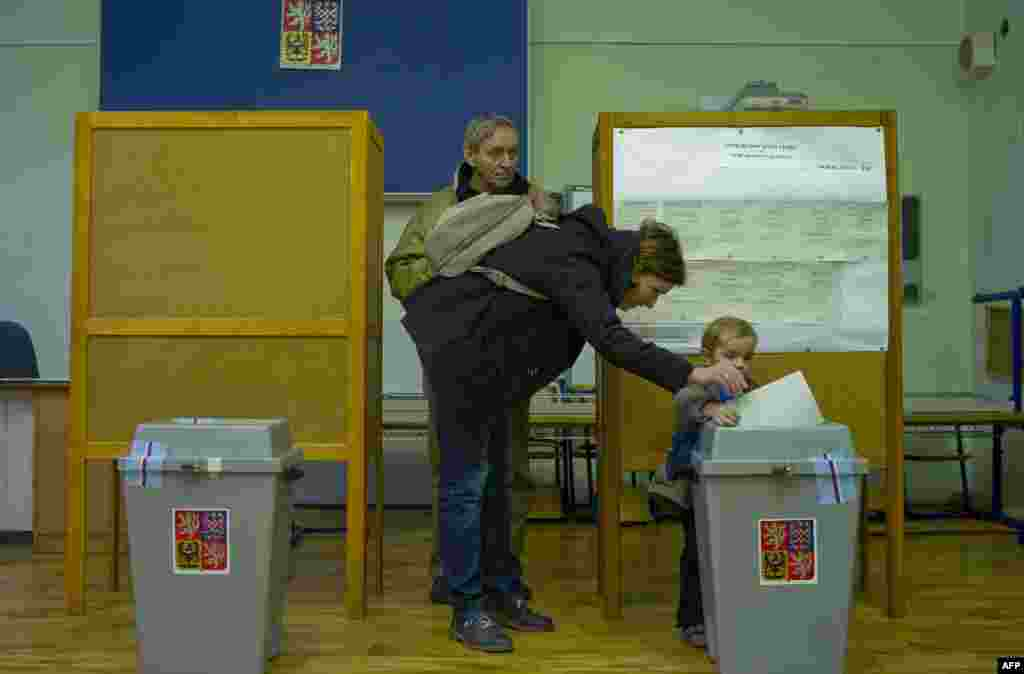 A mother casts a ballot at a polling station in Prague, accompanied by her son.