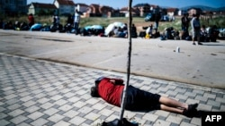 A migrant rests near the police station in the southern Serbian town of Presevo, near the border with Macedonia, on July 2.