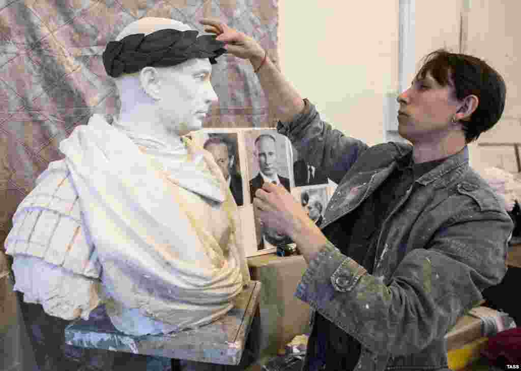 Sculptor Pavel Greshnikov finalizes a statue of Russian President Vladimir Putin in the style of a Roman emperor in the workshop of the Academy of Arts in St. Petersburg. The bust, which will be cast in bronze, is due to be unveiled outside a metro station on the northern outskirts of St. Petersburg on May 9, the holiday commemorating the Soviet victory in World War II. (TASS/Sergei Konkov)