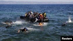 FILE: Afghan and Syrian refugees struggle to swim from a dinghy with a broken engine that drifts out of control to a rocky beach on the Greek island of Lesbos after crossing a part of the Aegean Sea from Turkey in September 2015